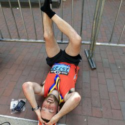 First-time marathon runner Dylan Maguire of Somerville, Mass. stretches his legs near the finish area of the 2012 Boston Marathon in Boston, Monday, April 16, 2012. (AP Photo/Elise Amendola)