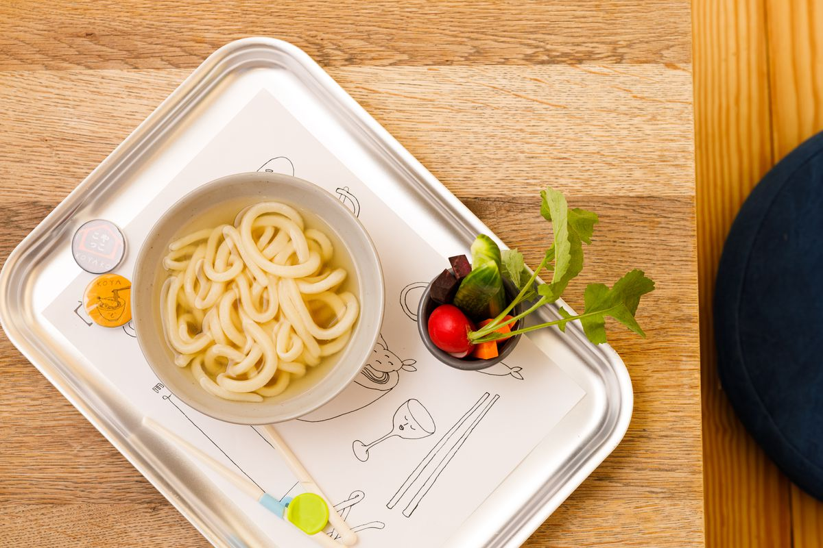 A kid's bowl of udon, with radish leaves poking out of a side dish of vegetables and playful drawings of chopsticks on the sheet of paper below the bowl.