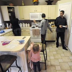 Jeff Griffin helps prepare the kitchen table for dinner with his wife Emily, son Bradley, 12, and 1-year-old daughter Katelyn in their home in West Jordan on Thursday, Feb. 27, 2014.