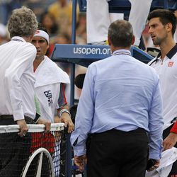 Spain's David Ferrer, second from left, and Serbia's Novak Djokovic, far right, talk with officials during a semifinal match at the 2012 US Open tennis tournament,  Saturday, Sept. 8, 2012, in New York. The match was suspended in the first set because of approaching inclement weather.