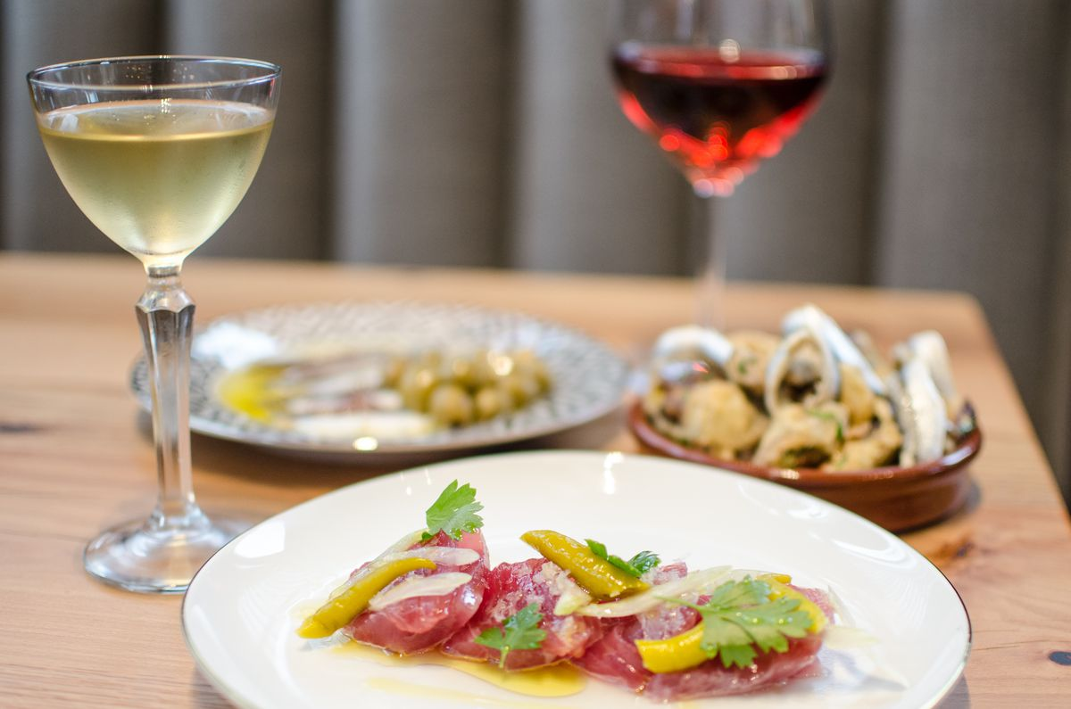 Three small tapas dishes sit on a light wooden table with a glass of white wine and red wine visible. The dish in the foreground is a tuna crudo, while the other two dishes are blurred in the background.