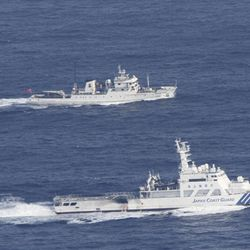 In this photo released by Japan Coast Guard, a Japan Coast Guard vessel, bottom, sails along with a Chinese fisheries patrol boat near disputed islands, called Senkaku in Japan and Diaoyu in China, in the East China Sea Tuesday, Sept. 18, 2012. The Coast Guard vessel issued a warning to the vessel near the islands early Tuesday.