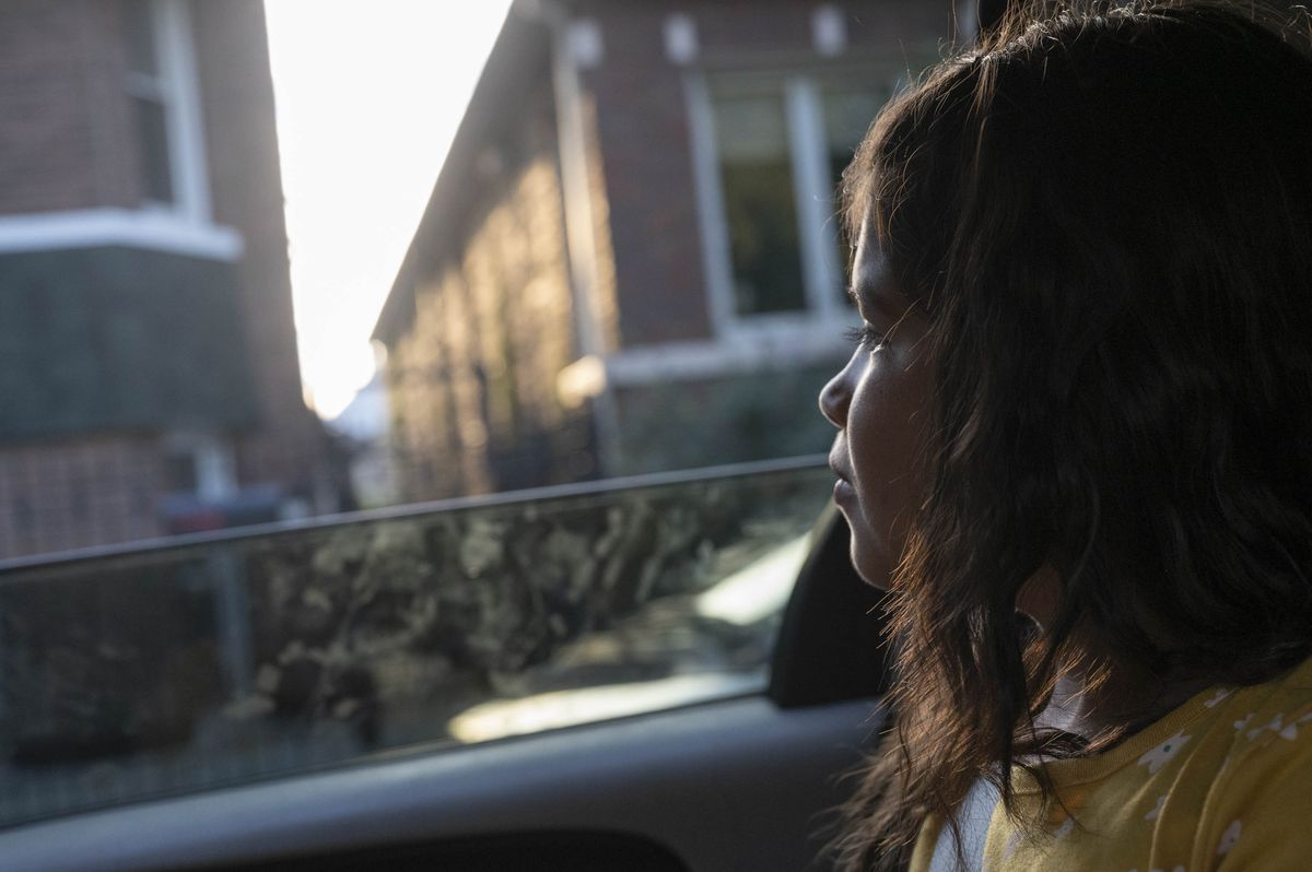 A young girl looks out the window of a car as early morning light outlines her face.