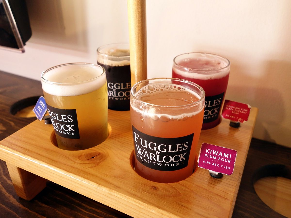 Four full glasses of beer stick out of holes in a wooden tray, with small labels afixed near each one.