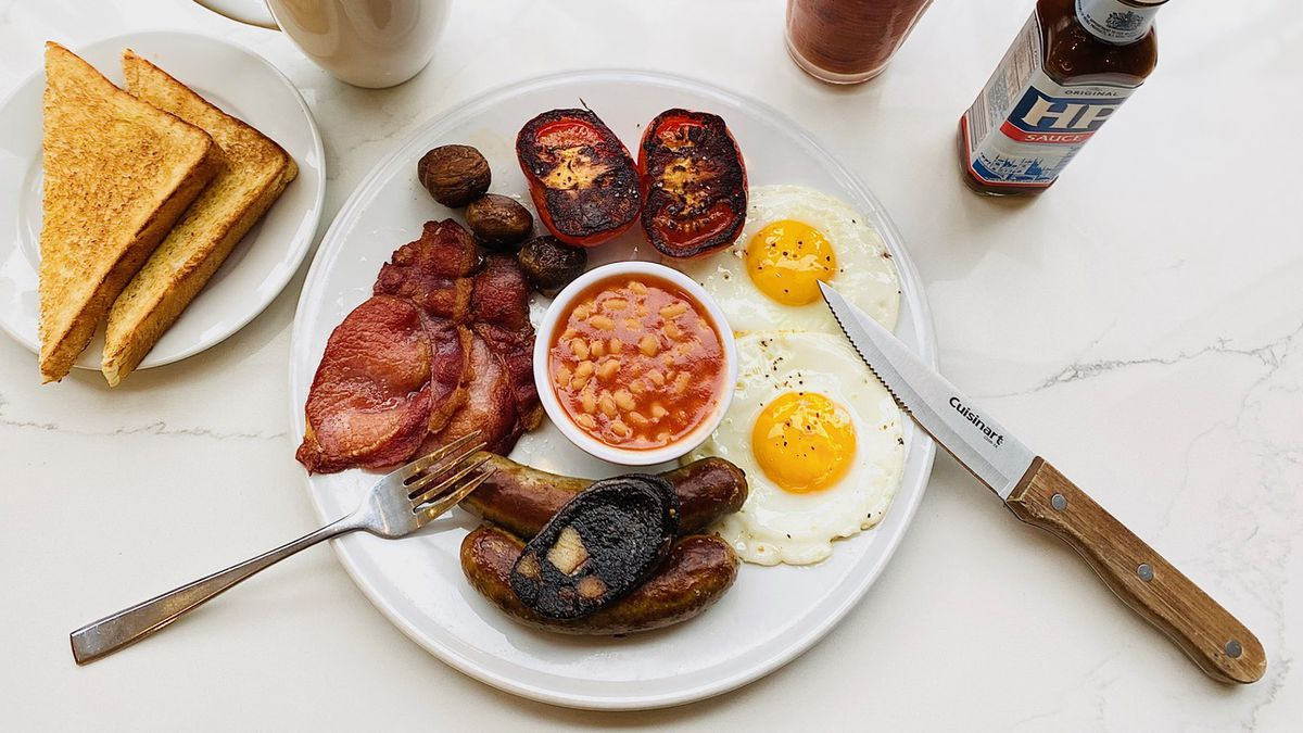 A white plate is packed with a container of beans, two fried eggs, two broiled tomatoes, rashers, black pudding and more, with a side of toast. This is the Full English at Kingsland Kitchen.