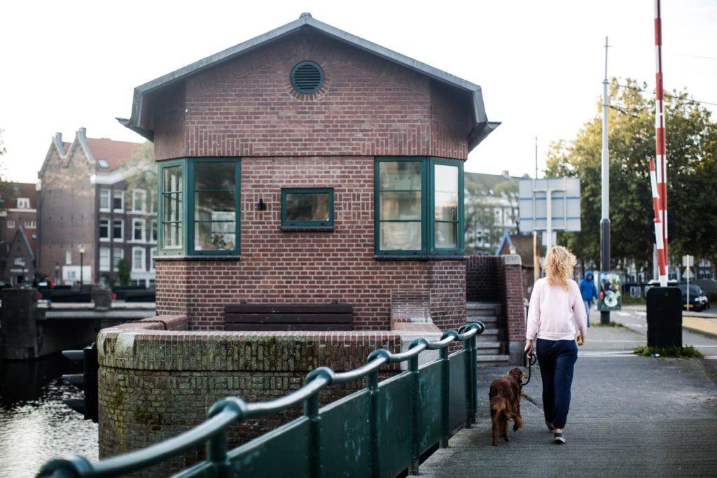 Brick bridge house and woman walking dog