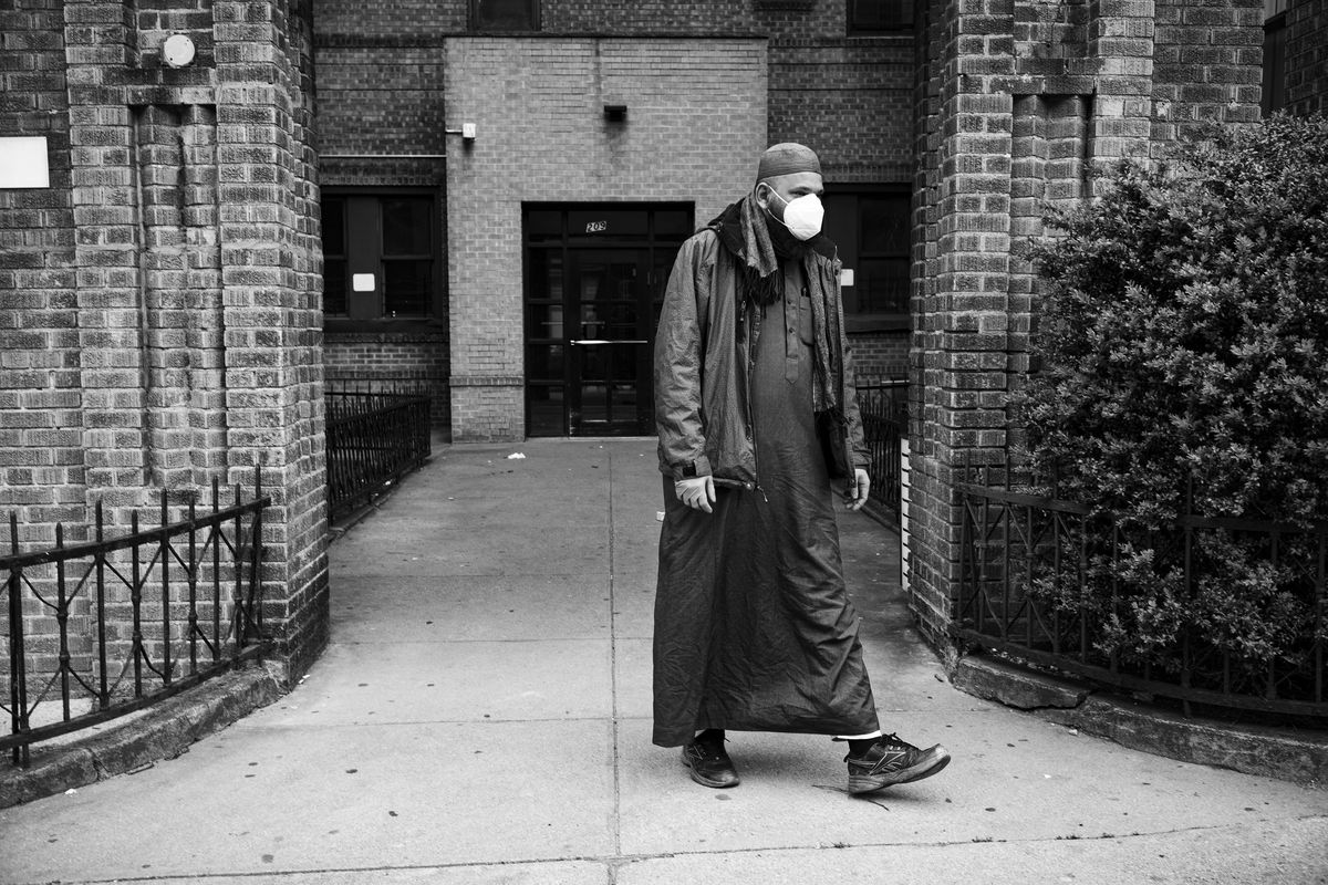 Imam Ahmed Ali Azur, wearing long clothing and a mask, in Brooklyn, New York, in April.