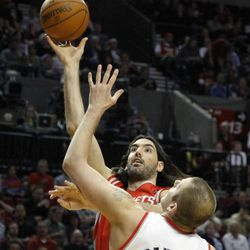Houston Rockets forward Luis Scola, left, from Argentina, shoots over Portland Trail Blazers center Joel Przybilla during the first quarter of their NBA basketball game in Portland, Ore., Monday, April 9, 2012.