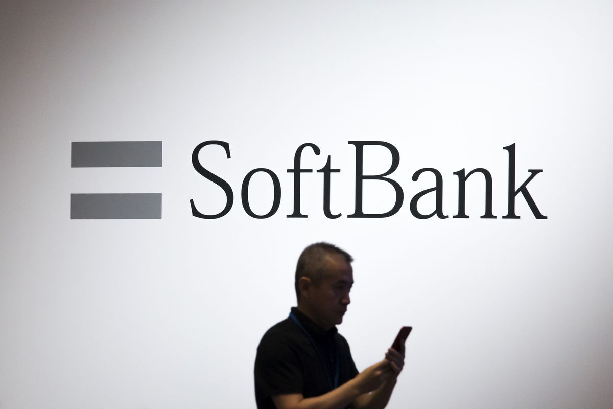 A man using a smartphone walks past the SoftBank Group Corp. logo during the SoftBank World 2017 conference on July 20, 2017, in Tokyo, Japan.