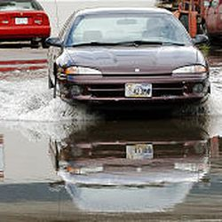 A motorist splashes through water near California Avenue and 1800 West. A nearby canal overflowed its banks, causing some flooding problems. At its high point Wednesday, the water reached many car doors.