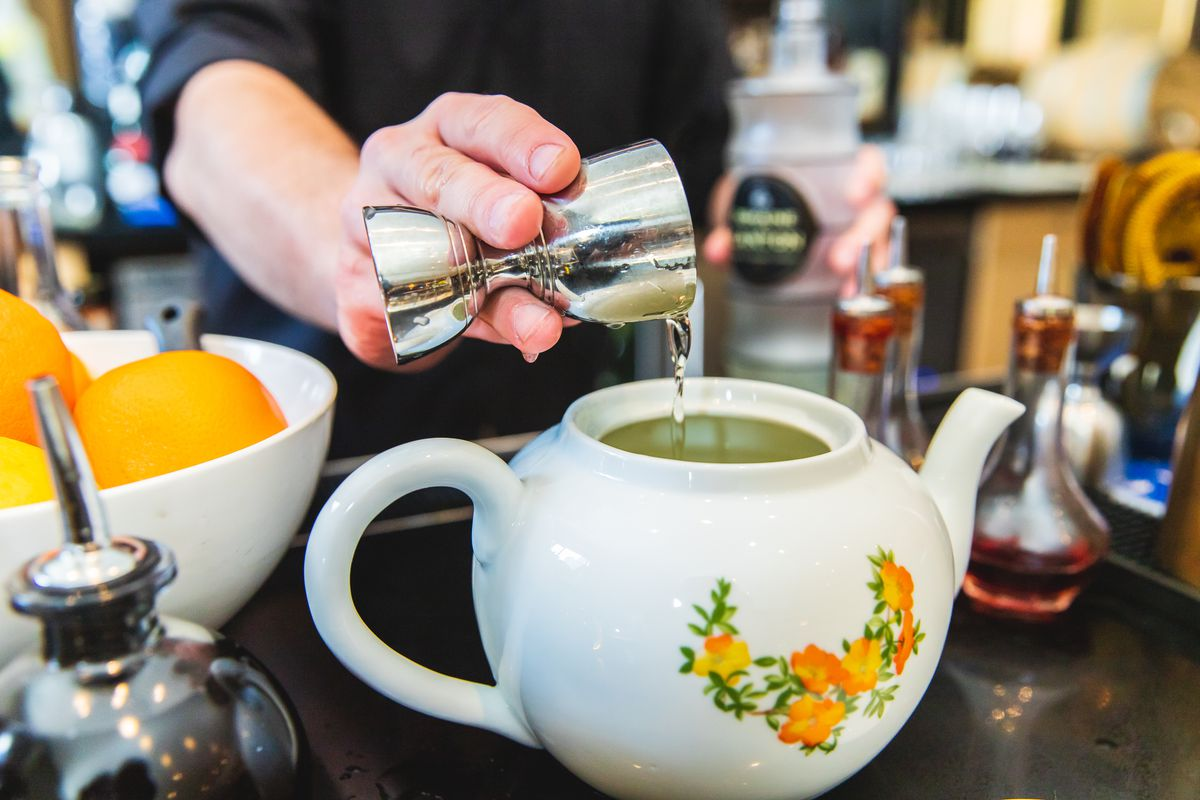 A bartender pours alcohol out of a jigger into a white ceramic teapot with orange flowers on the side.
