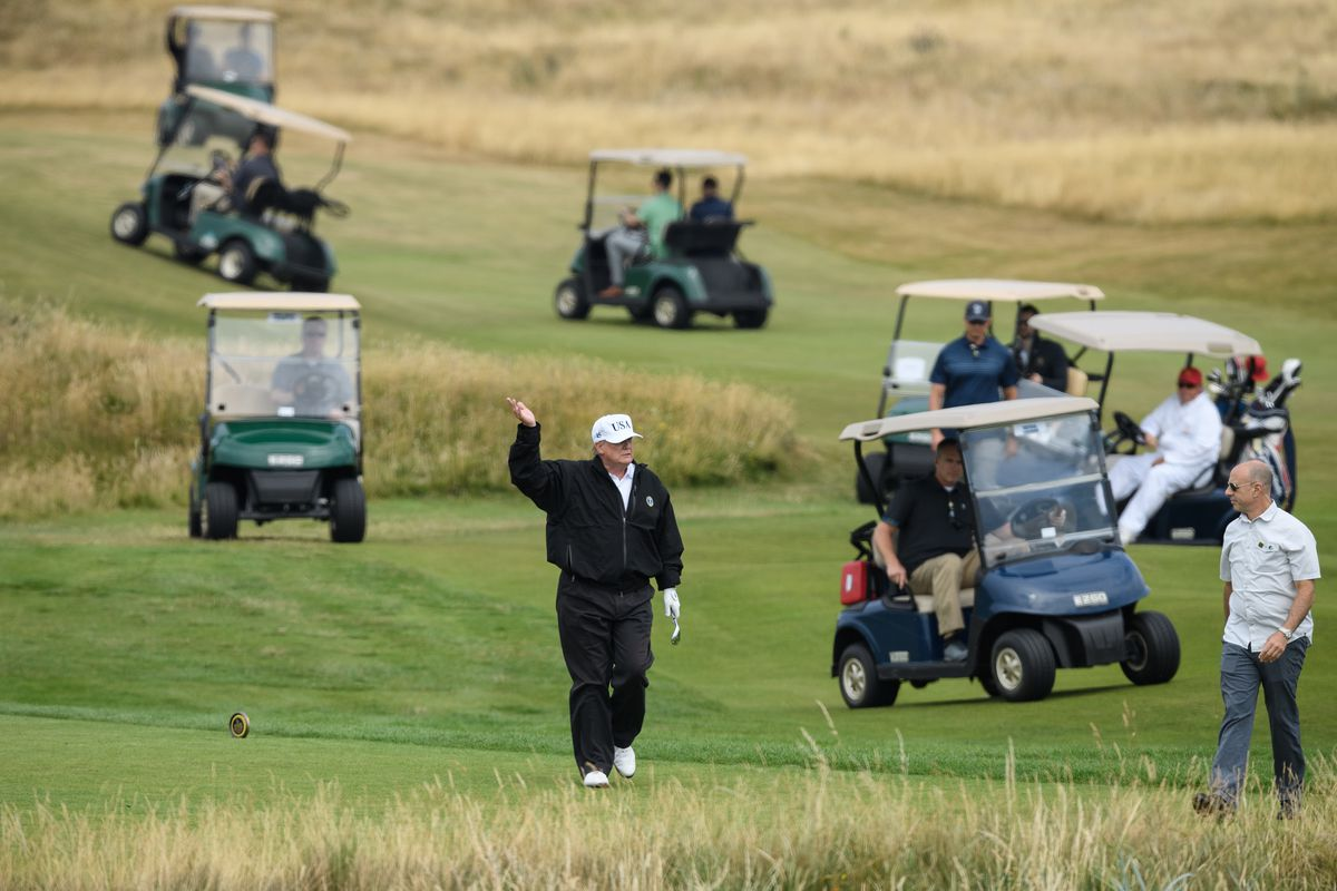 President Donald Trump, wearing a hat with Trump and USA displayed on it, plays golf at Trump Turnberry Luxury Collection Resort during the President's first official visit to the United Kingdom on July 14, 2018 in Turnberry, Scotland.