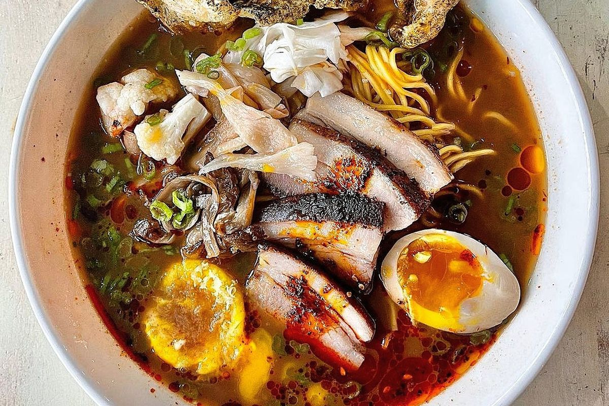 White bowl of ramen with deep brown broth, halved egg, pork belly, and yellow noodles