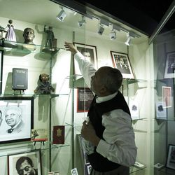 David Pilgrim, who is the founder and curator of the Jim Crow Museum of Racist Memorabilia, adjusts a display.
