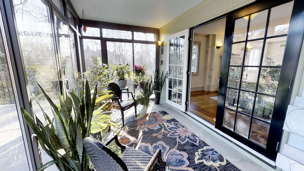 A sunroom with French doors and several planters.