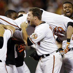 Baltimore Orioles' Chris Davis, center, carries Nate McLouth after Manny Machado, not pictured, scored a run on McLouth's single in the ninth inning of a baseball game against the Tampa Bay Rays in Baltimore, Wednesday, Sept. 12, 2012. Baltimore won 3-2.