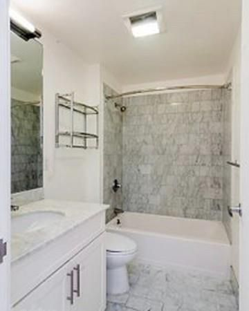 A narrow bathroom with the tub at the end, and there's no curtain on the tub.
