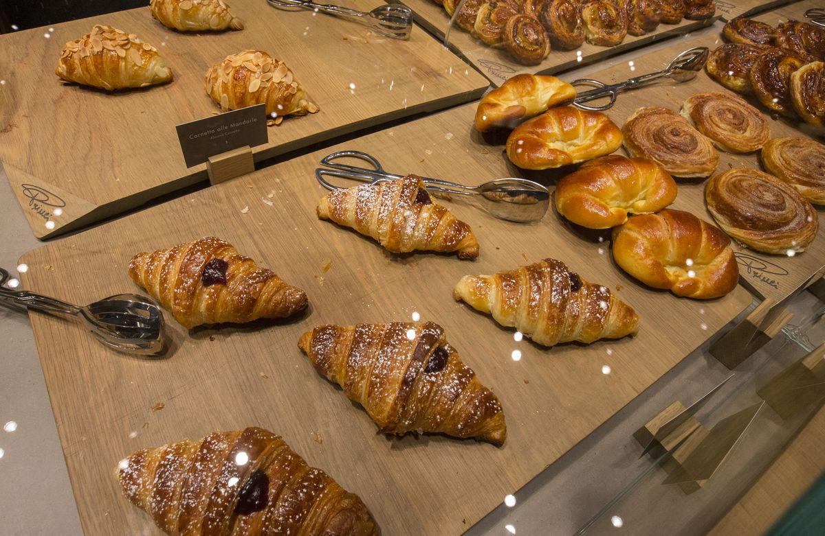 A selection of golden croissants, muffins, pastries, and more.