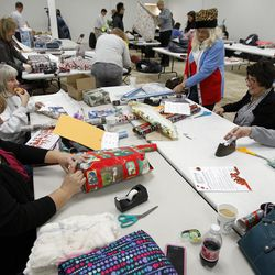 Volunteers wrap presents at the 13th annual Giving Tree program at Valley Fair Mall in West Valley City on Tuesday, Dec. 15, 2015.The program provides Christmas presents to 170 children from 61 low-income families in the city.