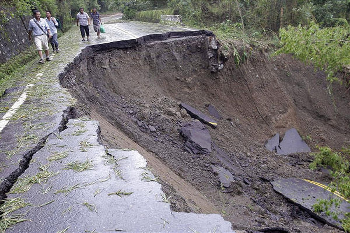 Residents from the flood-damaged area of Tainan County, Taiwan, walk on a destroyed mountain road Tuesday.
