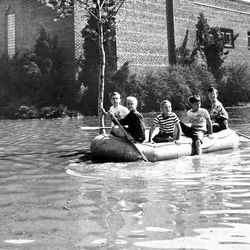 Young boys enjoy a casual ride in a raft on State Street near 1000 South on May 1, 1952. Major flooding created moments of fun for some.