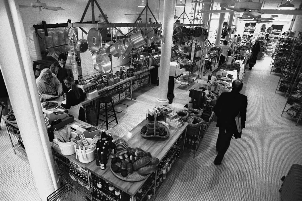 Elevated view inside the first Dean and DeLuca grocery store photographed in black and white with silver pots and pans hanging from the ceiling above a rectangular butcher block counter with baskets full of bread