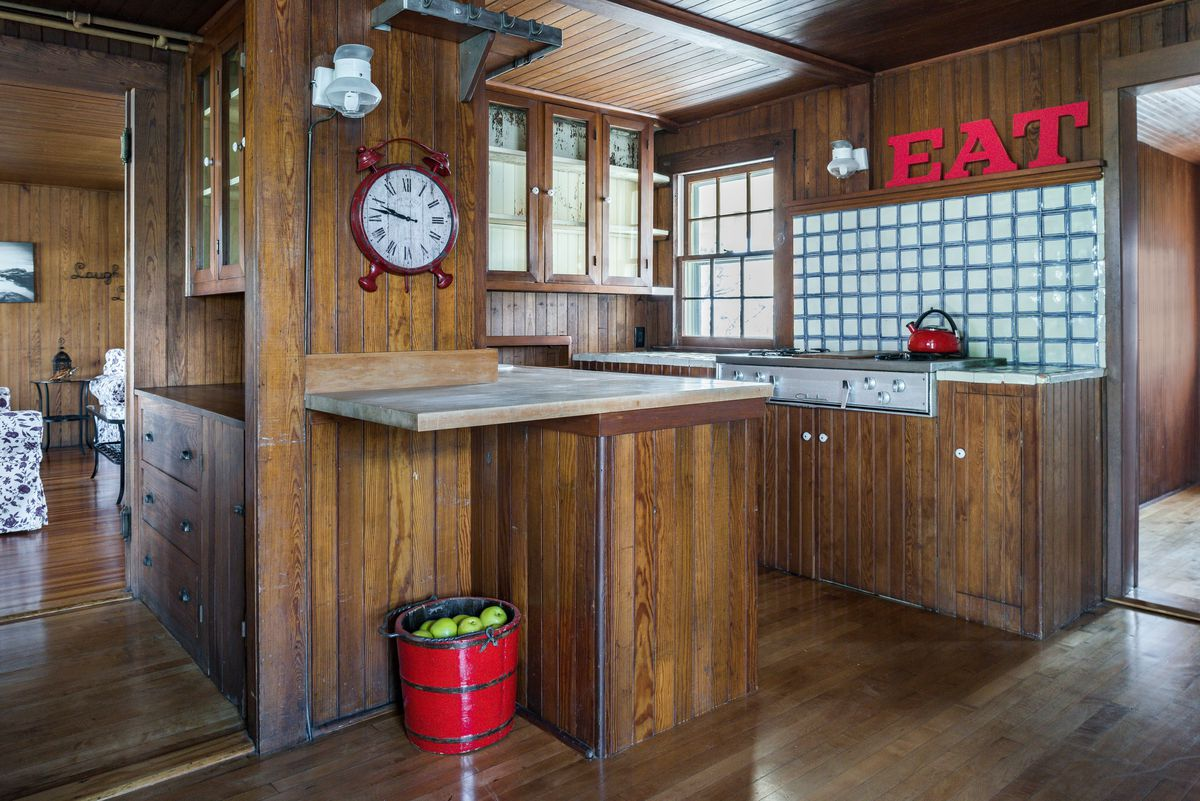 A small galley style kitchen has wood floors, and cabinets.