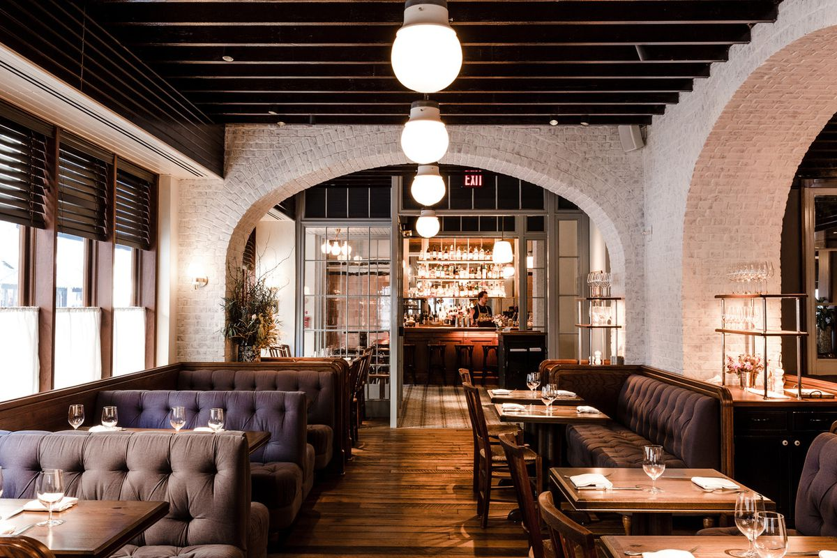 restaurant interior with brown booths and whitewashed brick walls with wide archways