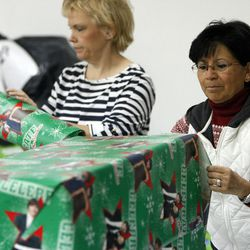 Volunteers wrap presents at the 13th annual Giving Tree program at Valley Fair Mall in West Valley City on Tuesday, Dec. 15, 2015. The program provides Christmas presents to 170 children from 61 low-income families in the city.