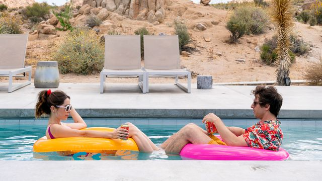Cristin Milioti and Andy Samberg, wearing bright swimwear and sunglasses, lounge on neon floats in a swimming pool in the arid desert in the Sundance premiere comedy Palm Springs.