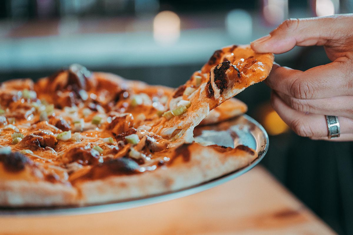 A cheesy slice of pizza being pulled away from a pie.