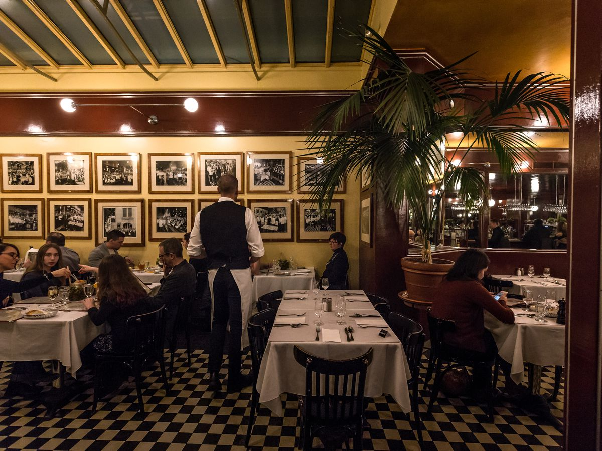 Inside L'Express restaurant, with a waiter in a suit, yellow walls, and old photos hanging on them.