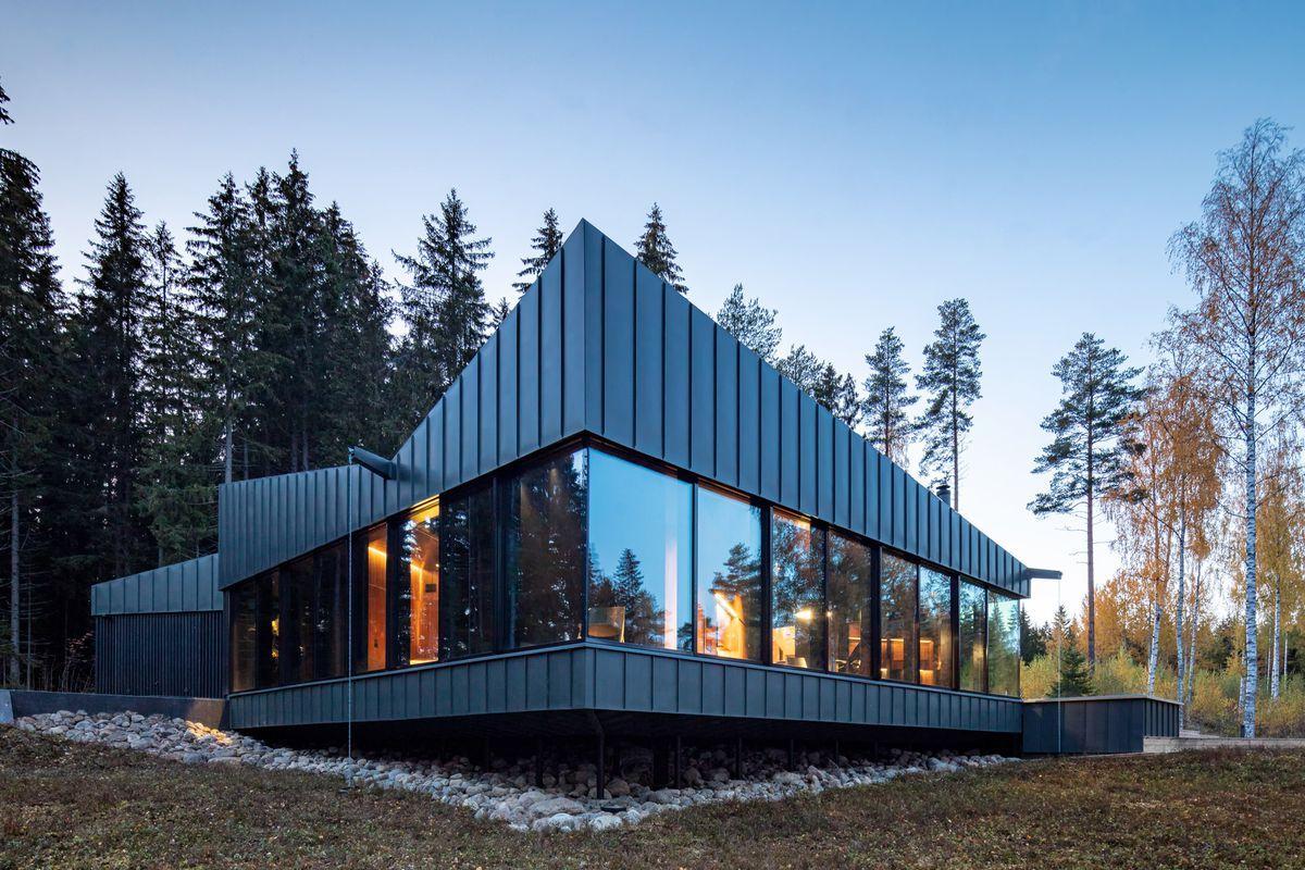 Home clad in windows and dark zinc siding.
