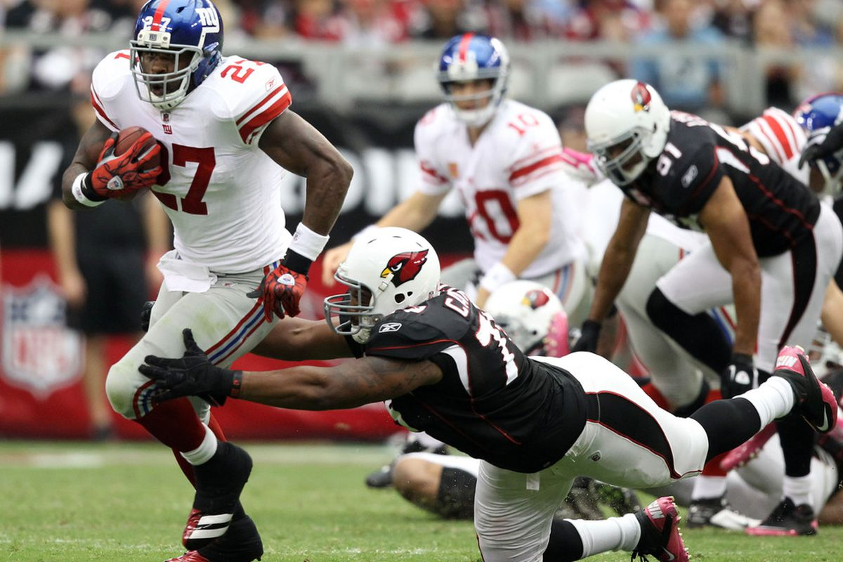 Brandon Jacobs of the New York Giants runs with the football against  David Carter of the Arizona Cardinals at University of Phoenix Stadium on October 2, 2011 in Glendale, Arizona.  (Photo by Christian Petersen/Getty Images)