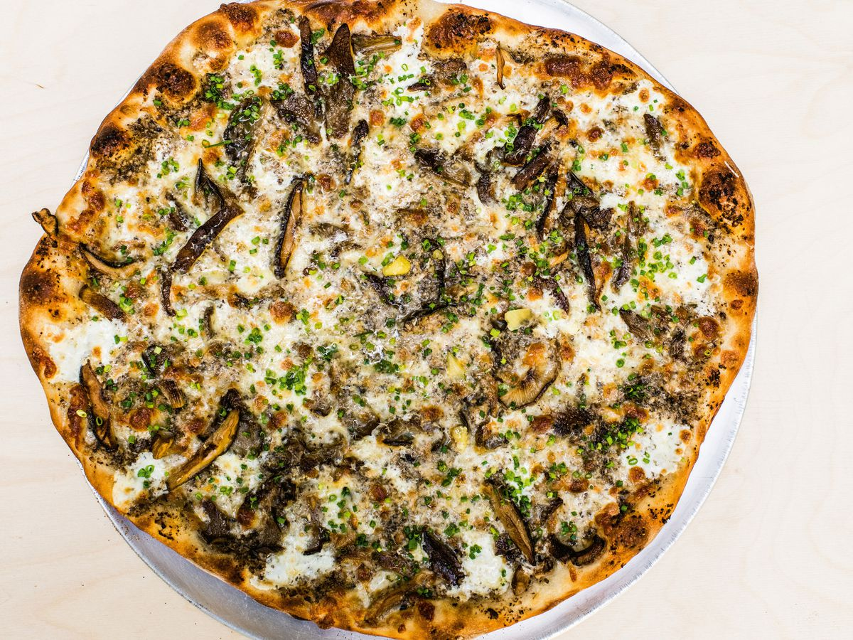 round pizza with mushrooms, scallions, and cheese
