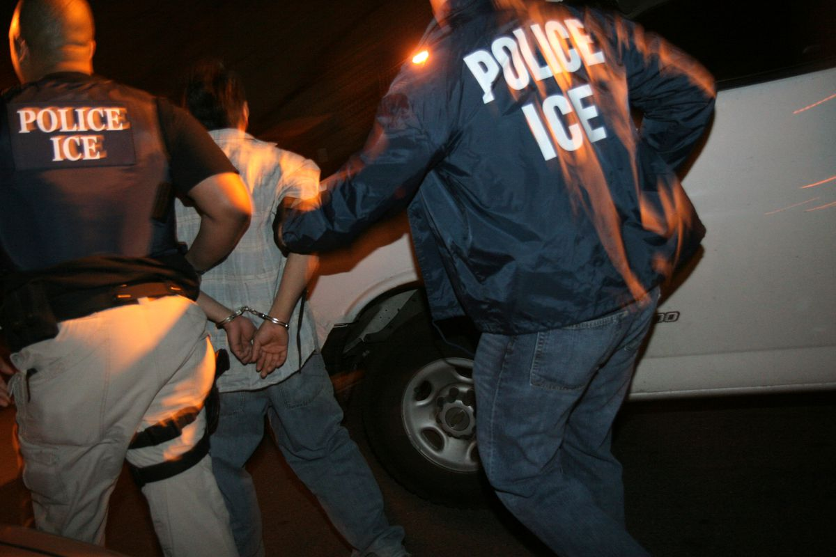 Two ICE agents arresting a man, pictured from behind.