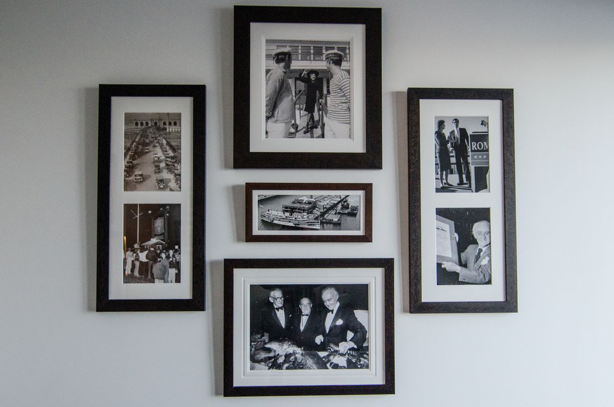 A wall of black and white photographs featuring restaurateur Anthony Athanas of Boston's Anthony Pier 4 with various celebrity guests