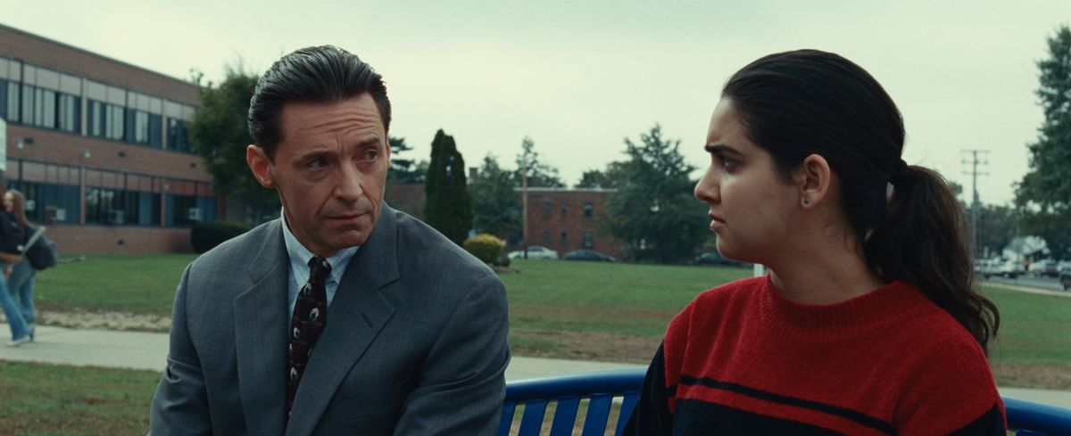 Hugh Jackman and Geraldine Viswanathan look on the outside bench in front of their HBO bad school.