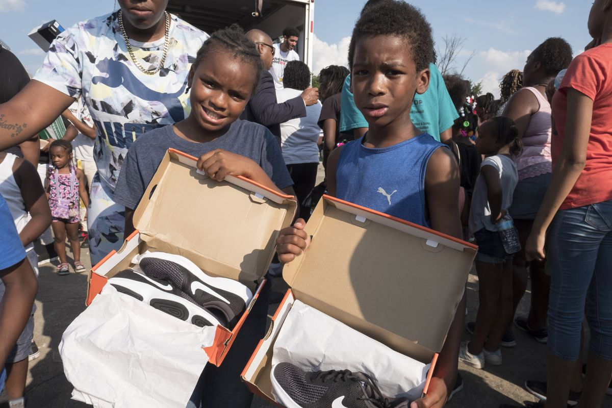 Pershais Comer, 9, and Cameron Comer, 8, posing with their new shoes they got from Vic Mensa's foundation, Save Money Save Lifes shoe give away event.   Rick Majewski/For the Sun-Times