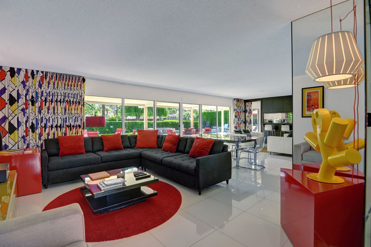 A living room with a black couch, red pillows, and white floors.