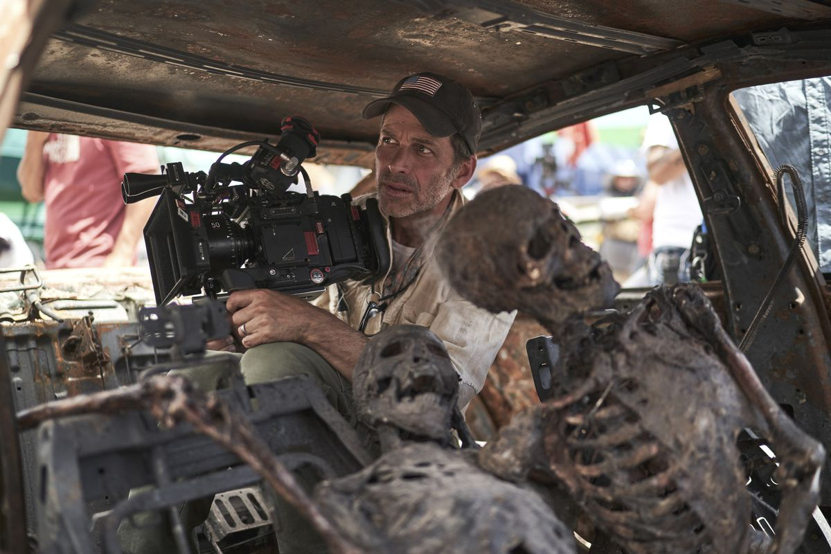 Zack Snyder sits in the back of a car behind two rotting skeletons on the Army of the Dead set