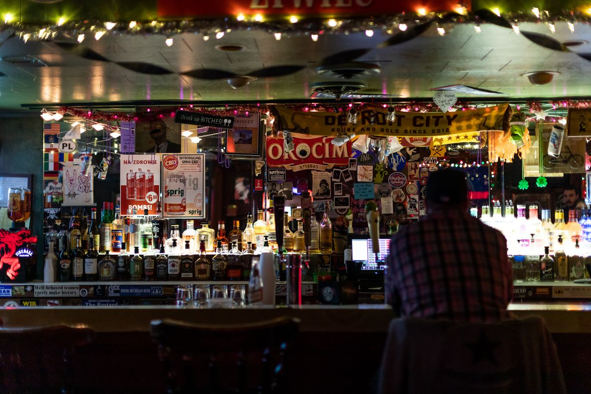 A man in plaid sits at the dark bar inside Whiskey in the Jar.