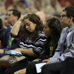 Ana Hernandez, left, sits with her children Stephanie and Louis, right, during the public memorial service for husband slain TSA officer Gerardo Hernandez, Tuesday, Nov. 12, 2013, in Los Angeles. Hernandez was the first TSA officer killed in the line of duty when a gunman pulled a rifle from a bag and shot the 39-year-old father of two on Nov. 1, at Los Angeles International Airport. Two TSA officers and a teacher were injured before airport police wounded the gunman, Paul Ciancia.