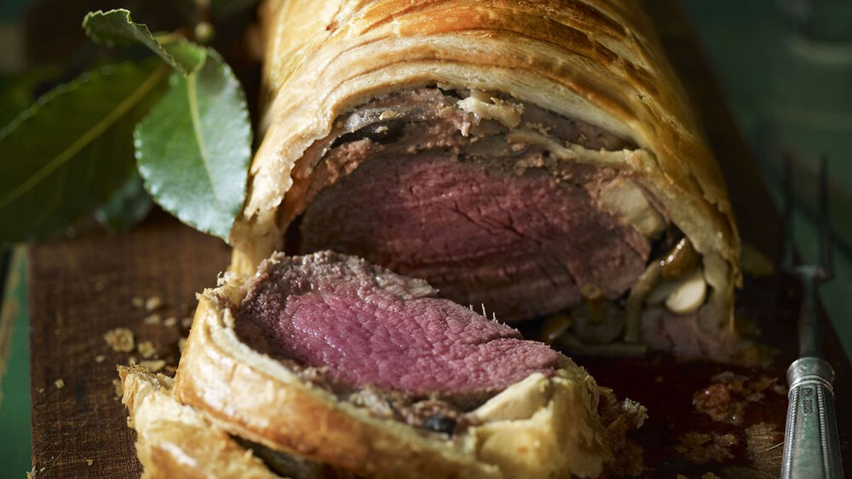 A pastry-wrapped, medium-rare cut of elk has been sliced in half on a wooden serving plate.