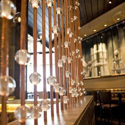 Copper pipes with acrylic orbs create division in the dining room.