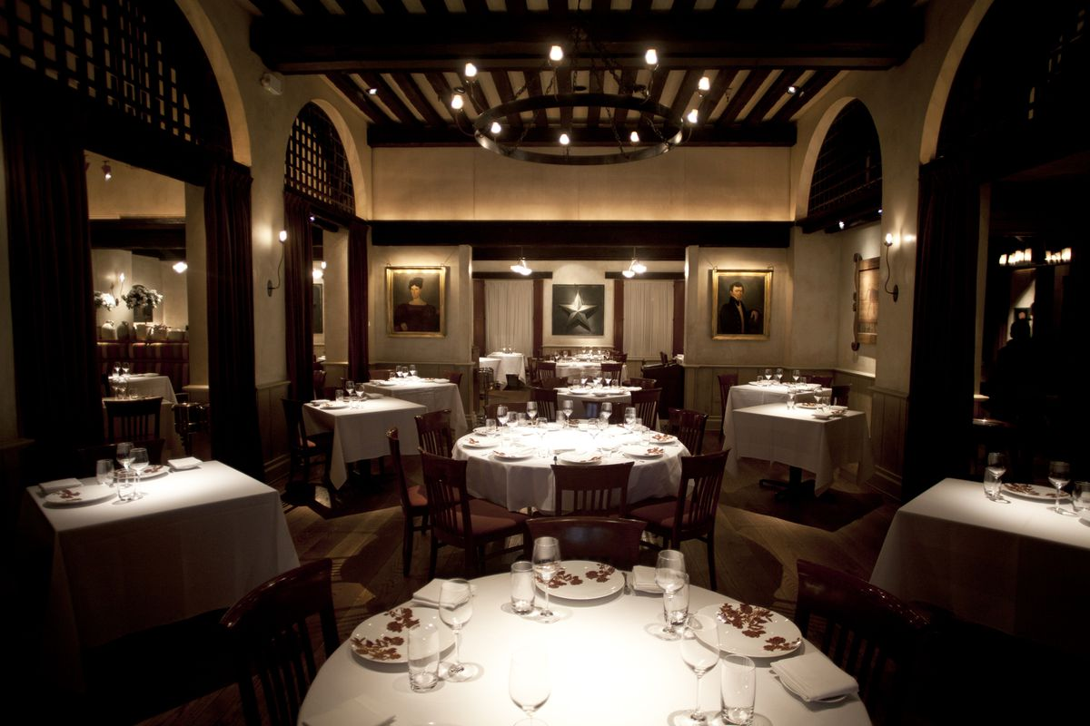 White tablecloth tables in a dark dining room