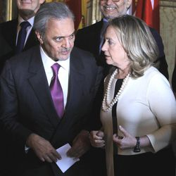 U.S Secretary of State Hillary Rodham Clinton, right, talks to Saudi Foreign Minister Saud al-Faisal as the attendees of an meeting on Syria gather for a  group photo  in Paris, Thursday, April 19, 2012.
