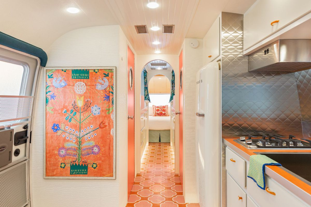 The hallway of the travel trailer has bright coral geometric flooring, white walls, a silver-backed kitchen, and a bright orange piece of artwork.