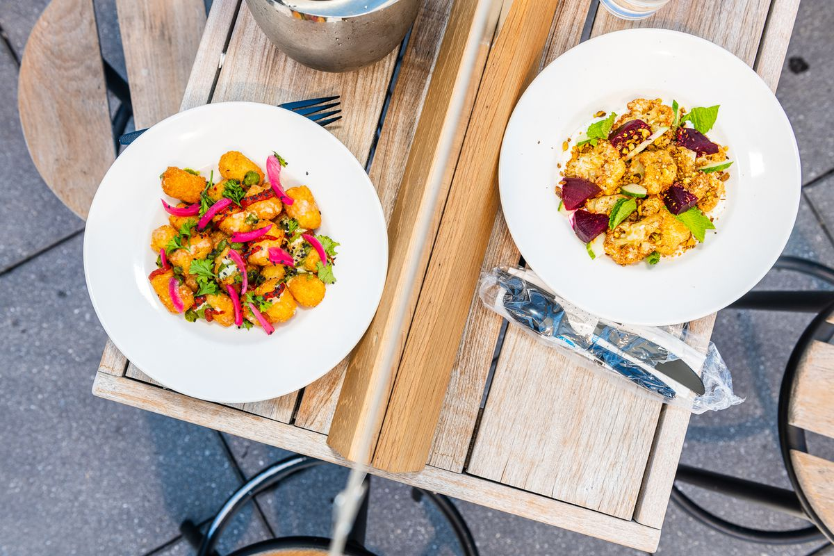 Tetatots, left, and roasted cauliflower sit on a table divided by a sheet of plexiglass on the roof at Brixton
