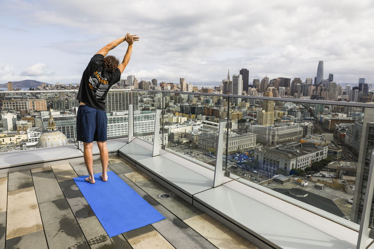 A person on a rooftop deck with a view of the San Francisco skyline stretches while standing on a yoga mat.